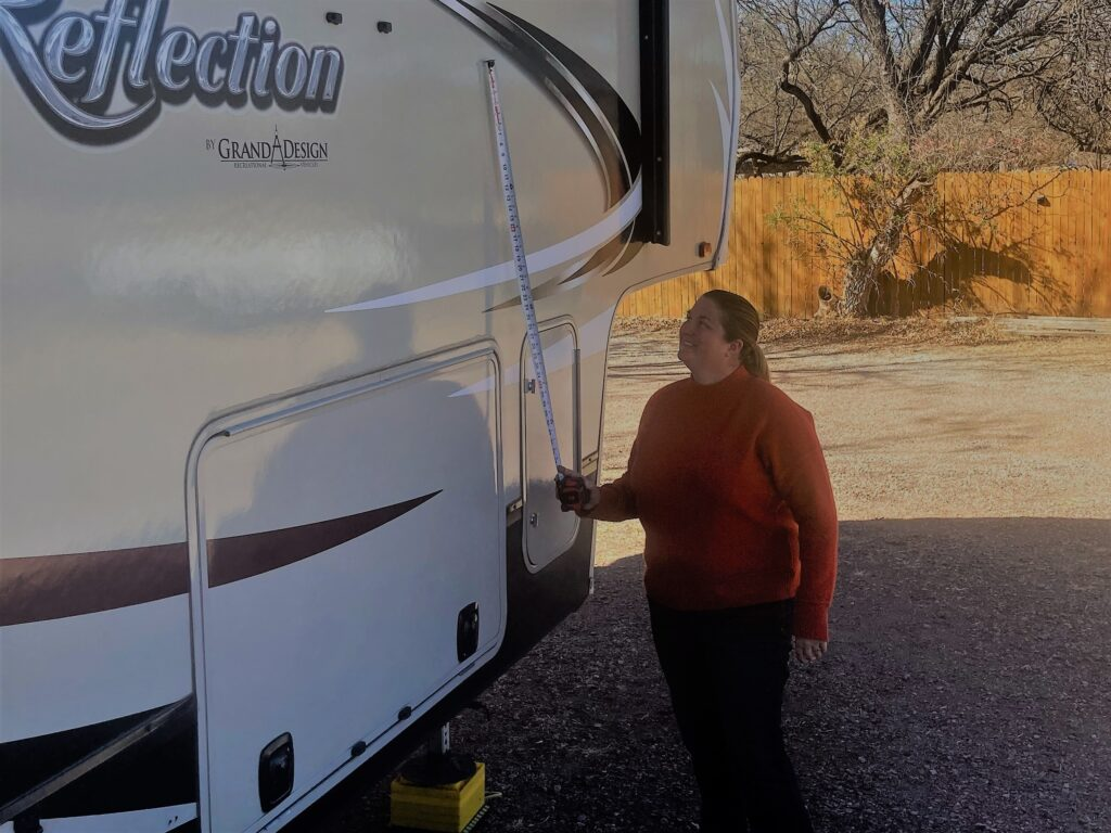 Woman Measuring How Tall an RV Is