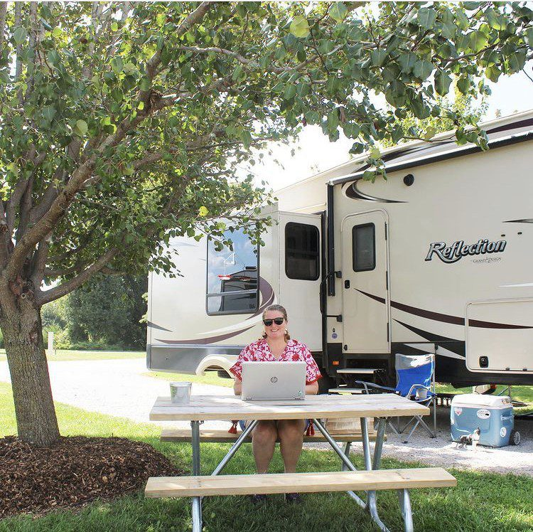 Woman sitting at picnic table with laptop at RV Campsite