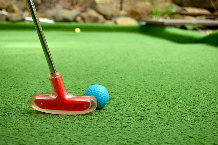Red mini golf putter and blue ball