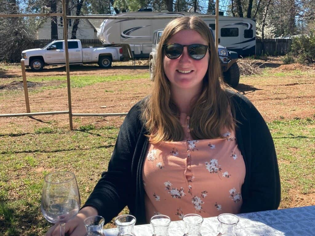 Woman drinking a wine flight at a Harvest Hosts location with RV camping